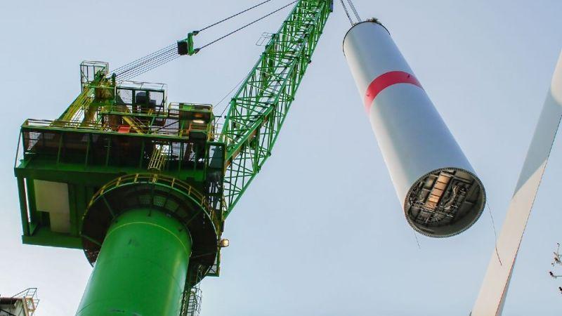 Der Turm einer Windenergieanlage hängt an einem Kran.