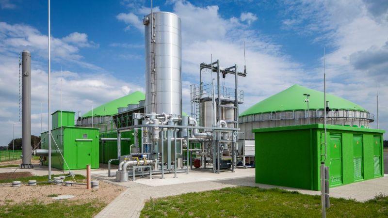 Das Foto zeigt eine Gasaufbereitungsanlage einer Biogasanlage, im Hintergrund sind Fermenter zu sehen.
