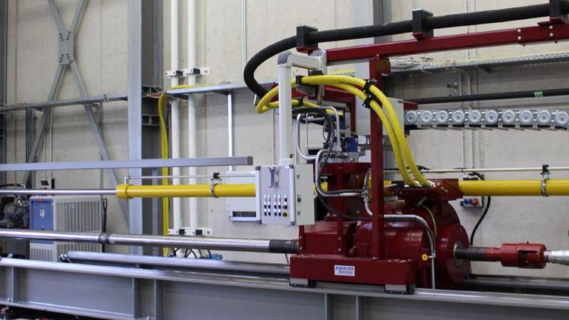 Ausgangskonfiguration des Teststands. Die Tests werden mit einer waagerecht montierten Bohranlage durchgeführt. Der Antrieb (rot, mittig im Bild) treibt das Bohrgestänge an, das aus der Halle heraus auf das Testgelände ragt.