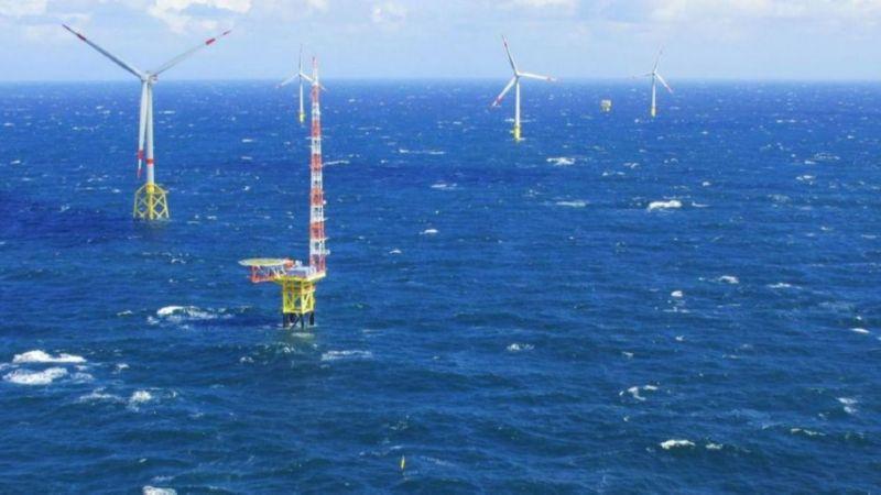 Eine Forschungsplattform in der Nordsee in unmittelbarer Nähe zu einem Windpark.