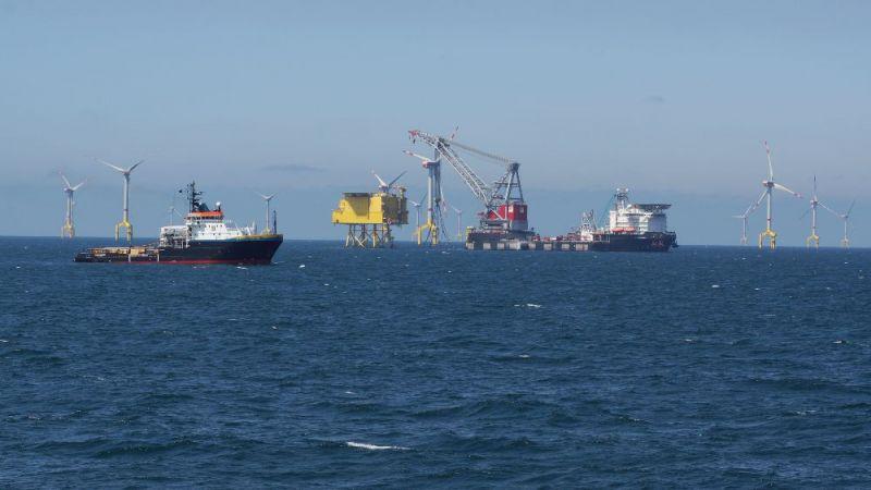 Auf dem Foto sind mehrere Schiffe zu sehen, die gerade einen Offshore-Windpark aufbauen.