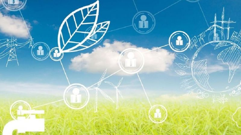 Das Symbolbild zeigt Symbole aus dem Energiebereich vor blauem Himmel und grüner Wiese.
