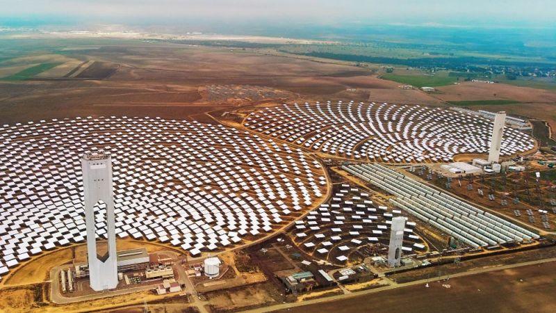 Das Bild zeigt ein solares Kraftwerk mit Turm und Heliostatenfeld.
