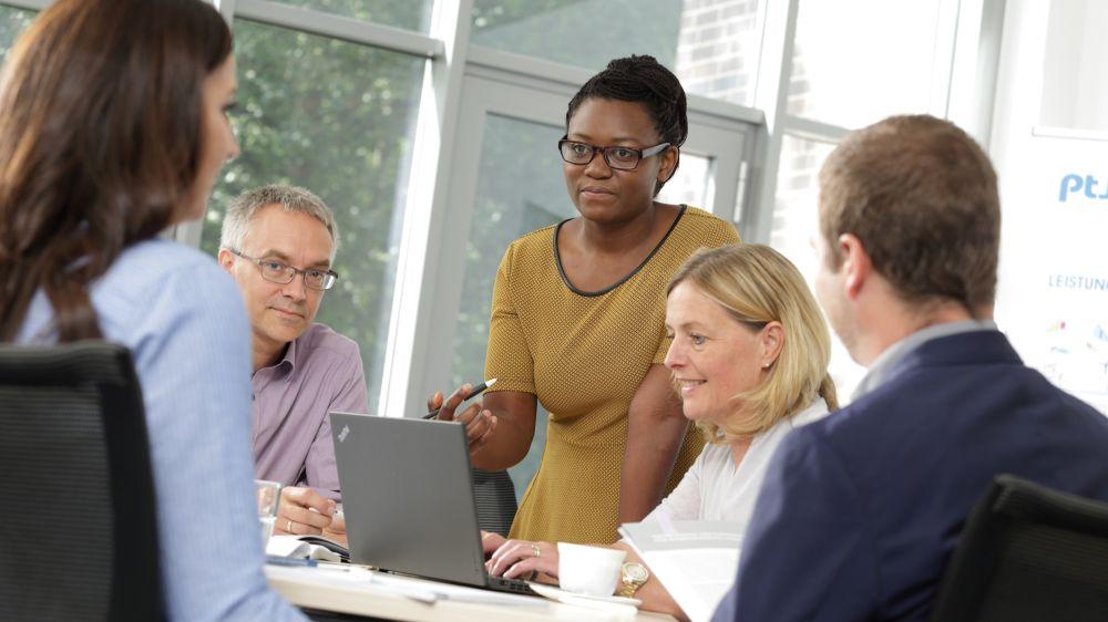 Das Bild zeigt eine gestellte eine Gesprächssituation mit vier Personen vor einem Laptop