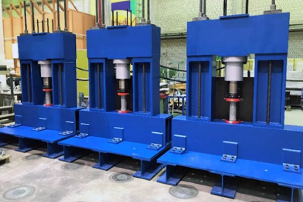 Das Foto zeigt einen Mehrfachprüfstand für die zyklische Beanspruchung von insgesamt drei Betonzylindern.