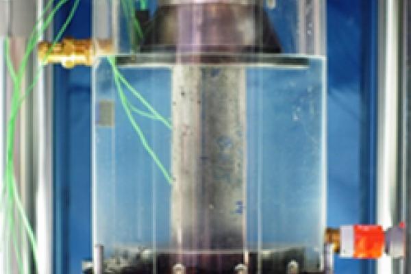 Das Foto zeigt den Aufbau eines Ermüdungsversuchs an einem Betonzylinder unter Wasser.