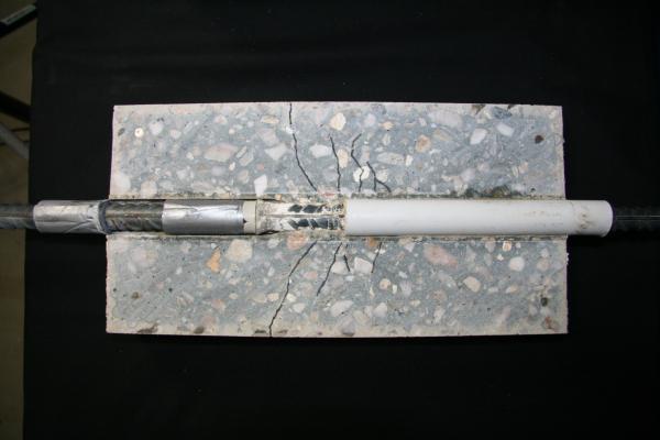 Das Foto zeigt einen Verbundbereich nach Auszugversagen mit Rissen (nachgezeichnet).