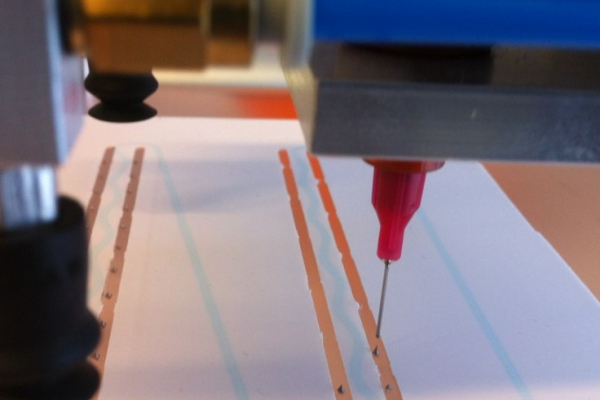 Im Labor wird über eine feine Düse der Leitkleber auf ZEBRA IBC Solarzellen aufgetragen. Es entstehen feine Doppellinien.